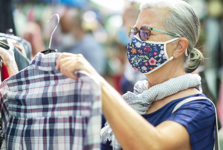 Close-up of senior woman wearing mask standing at store