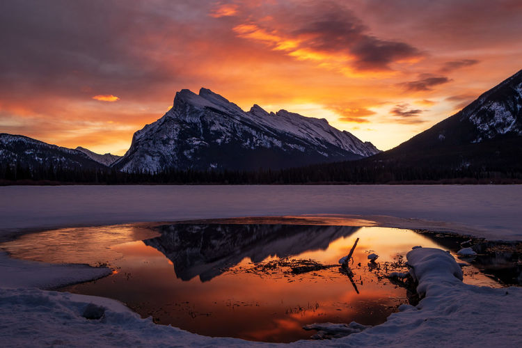 Scenic view of lake by mountains against orange sky