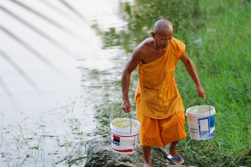 Full length of monk carrying water buckets