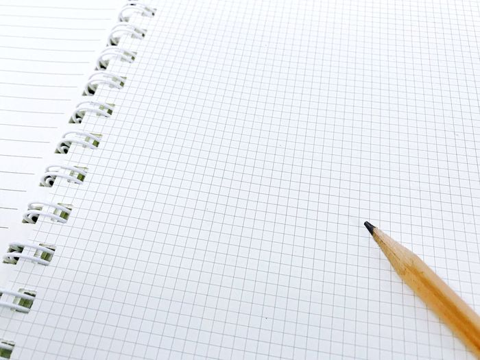 High angle view of pencil on spiral notebook