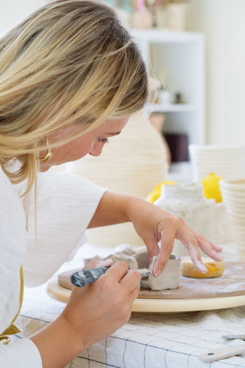 Female pottery artist making a vase in her home studio