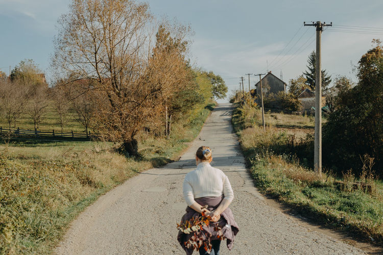 Rear view of woman riding horse on road