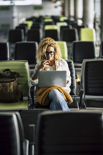Smiling woman using laptop while sitting at airport