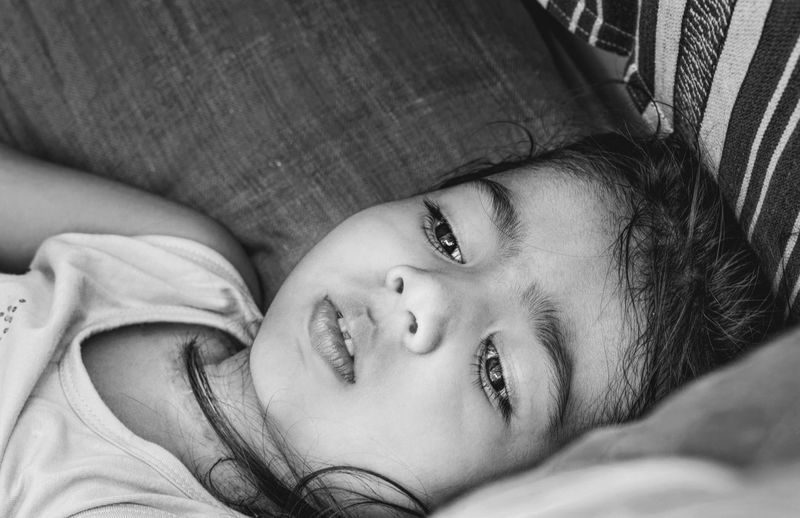 Portrait of baby girl lying on bed at home