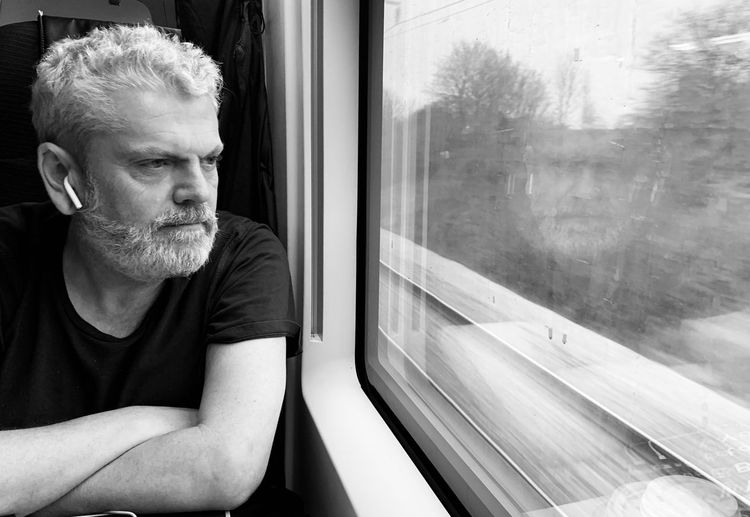 Man Looking Through Train Window