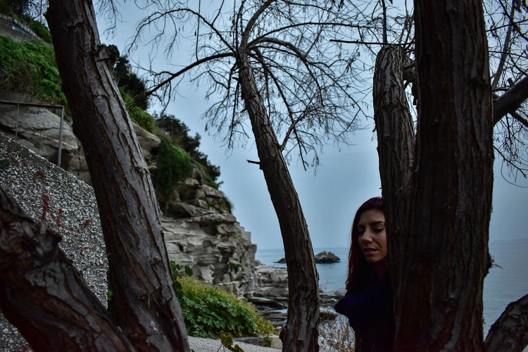 Woman standing by tree trunk against sky