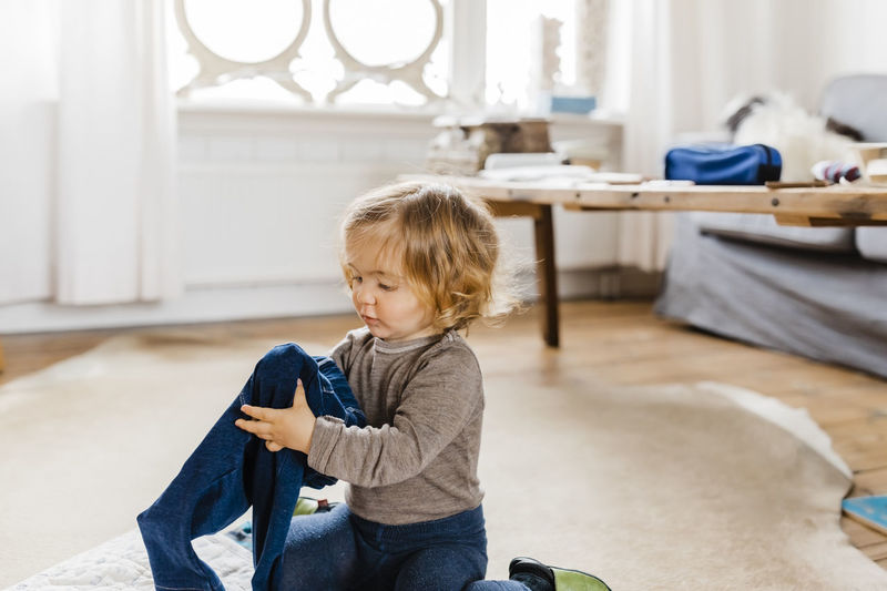 Girl Holding Jeans While Sitting At Home