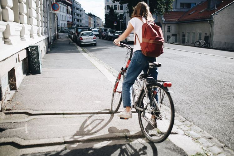 Young Woman With Bicycle On Road In City