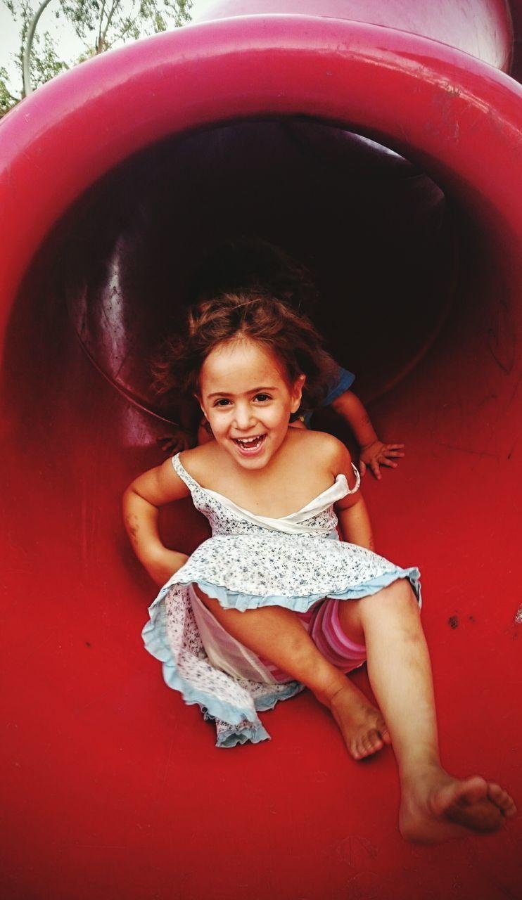 Full Length Portrait Of Girl Enjoying Slide In Park