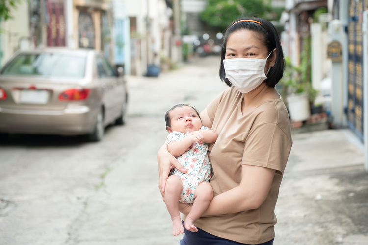 Asian mother wearing surgical face mask holding her baby, covid-19 concept