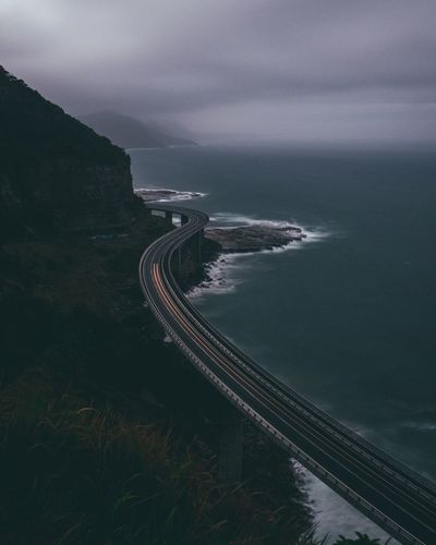 Aerial view of road by sea against cloudy sky at dusk