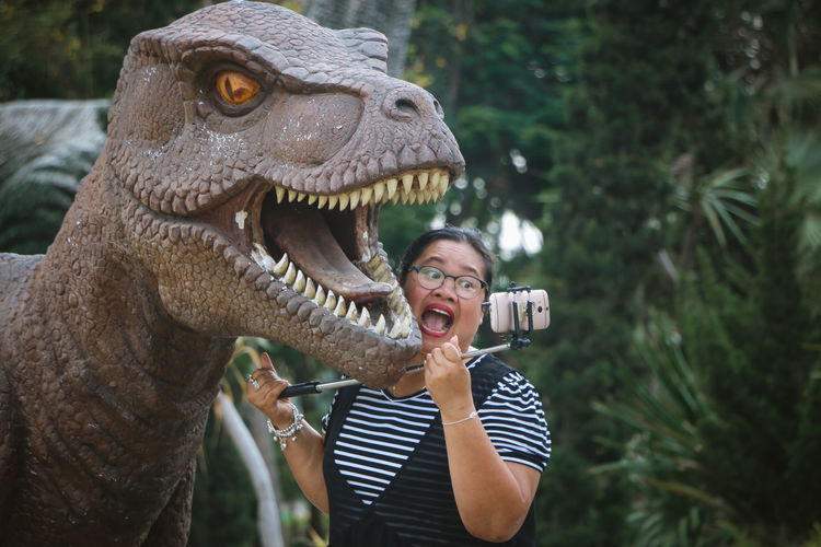 Woman taking selfie with dinosaur statue in park