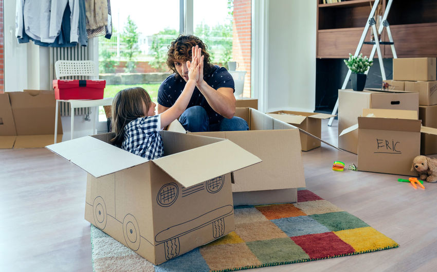 Father and son giving five after playing car racing with cardboard boxes Family Fun Funny Happiness Happy Horizontal Moving Unpacking Apartment Boxes Boy Cardboard Home Interior House Indoors  Lifestyles Living Room Mammal New Home Packing Placing Race Real People Relocating Two People