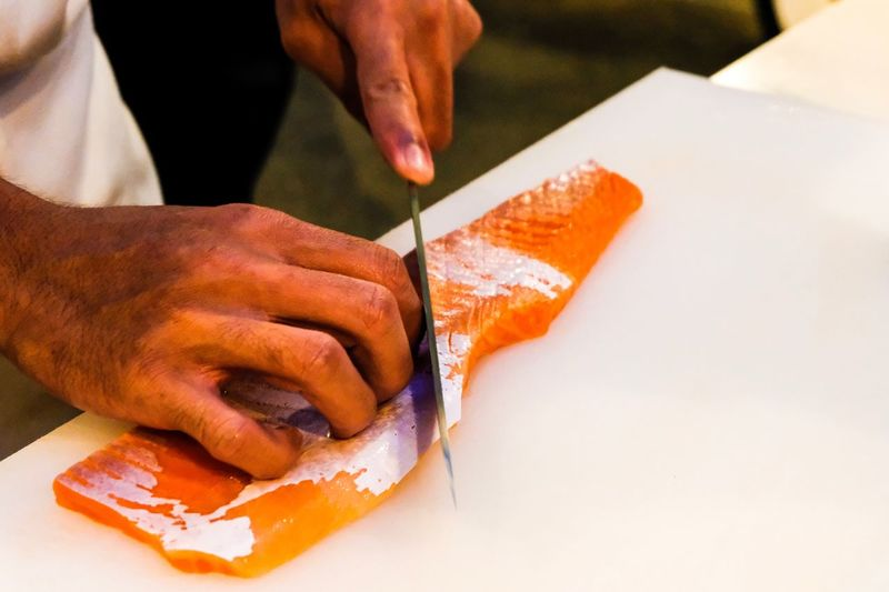 Slice or dice orange salmon Restaurant Orange Salmon Fresh Salmon Human Hand Human Body Part Hand One Person Indoors  Food Holding Food And Drink Close-up Occupation Cutting Freshness Preparation  Adult Working Finger Body Part Archival Making Men