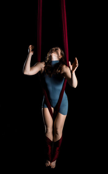 Young Woman Hanging On Fabric While Dancing Against Black Background