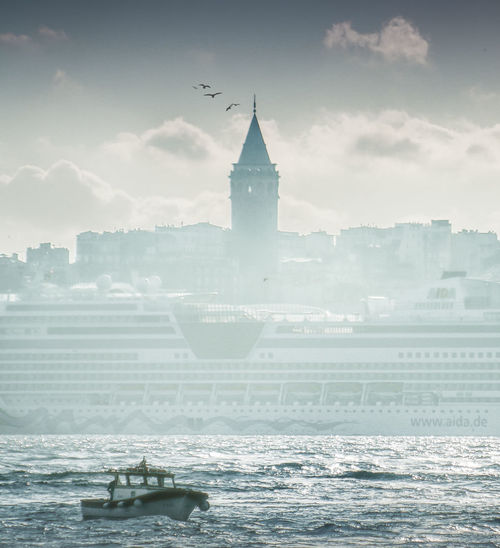 View of buildings in sea against cloudy sky