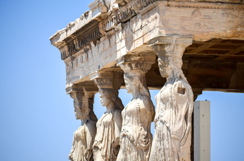 Acropolis, Athens Ancient Civilization Ancient Rome Arch Architectural Column Architectural Feature Architecture Athens, Greece Blue Building Exterior Built Structure Cariatides Clear Sky Columns Day Famous Place Historic Historic Building History Low Angle View Medieval Spanish Culture Statue Stone Material Travel Destinations