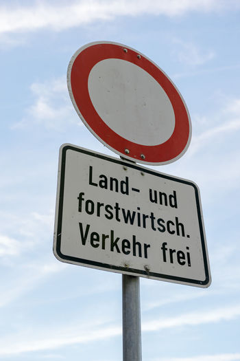 A road sign that says - No thoroughfare - except agricultural and silvicultural traffic in german language in front of blue sky. Sign No Thoroughfare Agricultural Silvicultura Silvicultural Measures Road Traffic Circle German Language Color Forbidden Information Prohibited Prohibition Red Symbol Transport Cloud - Sky Road Sign Information Sign Low Angle View Warning Sign Road Warning Sign Guidance Text