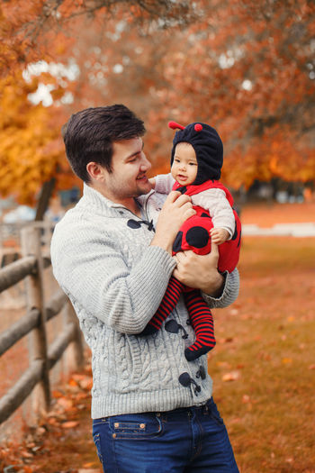 Father carrying cute daughter while standing in park during autumn