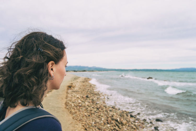Girl looking at the sea on a cloudy and sad day with the rough sea