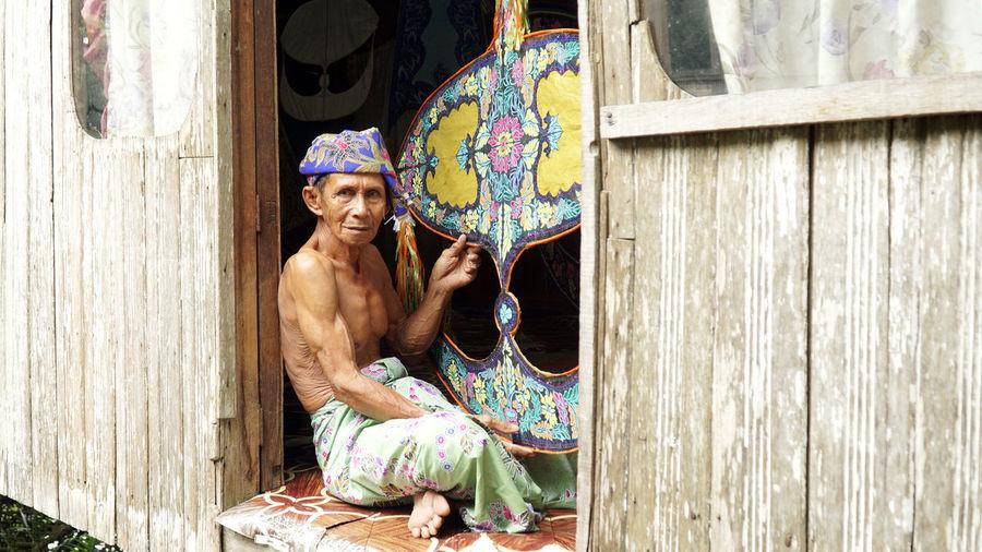 Shirtless man making craft product in workshop