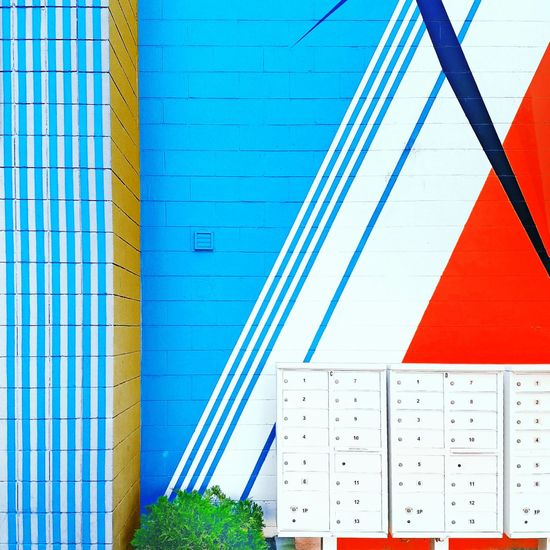 The Color Of Business Blue Tree Architecture Day City Life Outdoors Modern No People High Section Brick Wall Land Vehicle People And Places Man Made Object Geometric Shape Multi Colored Group Of Objects Vibrant Color Lifestyles Tranquil Scene Casual Clothing Mode Of Transport Communication Growth City