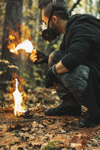Man wearing mask while holding fire in forest