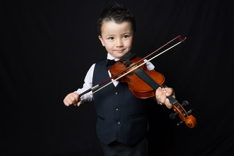 Portrait Of Boy Playing Violin Against Black Background