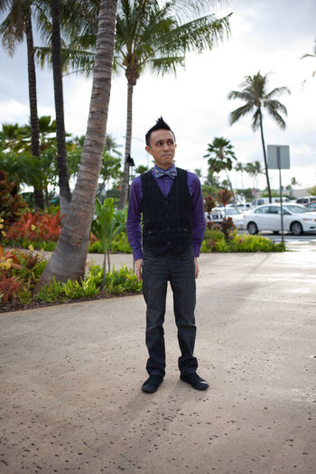 Full length portrait of young man standing on palm tree