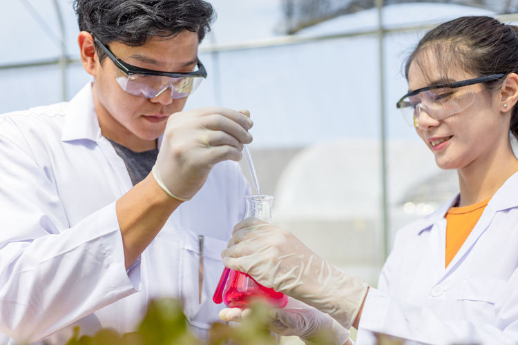Low angle view of scientists holding flask and pipette