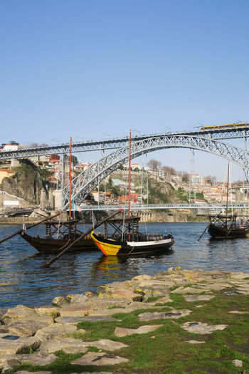 wooden rabelo boats in front of ponte dom luis in porto, portugal Rabelo Boat Porto Portugal Wooden Boat Port Wine Transportation Typical Attraction Ponte Dom Luis Barrel Douro River City Water Nautical Vessel Clear Sky Cityscape River