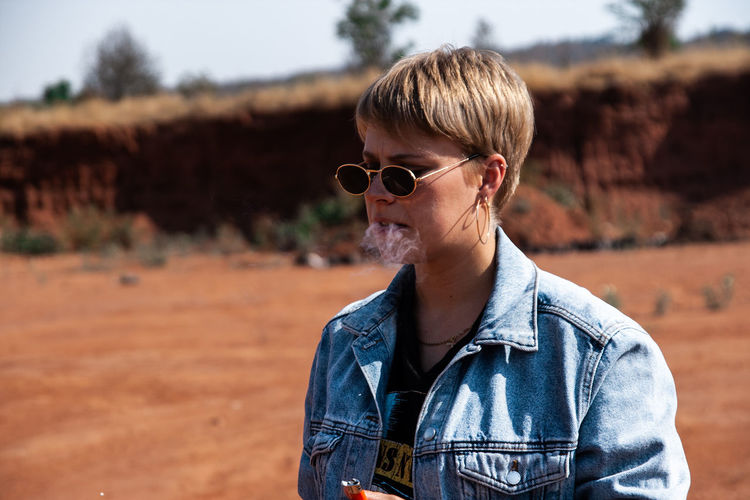 Young woman wearing sunglasses smoking while standing outdoors
