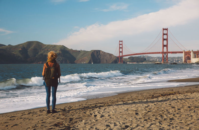 Woman Standing On Shore With Golden Gate Bridge In Background