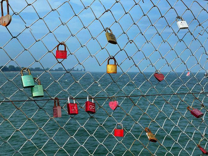 Padlocks hanging on chainlink fence against sky
