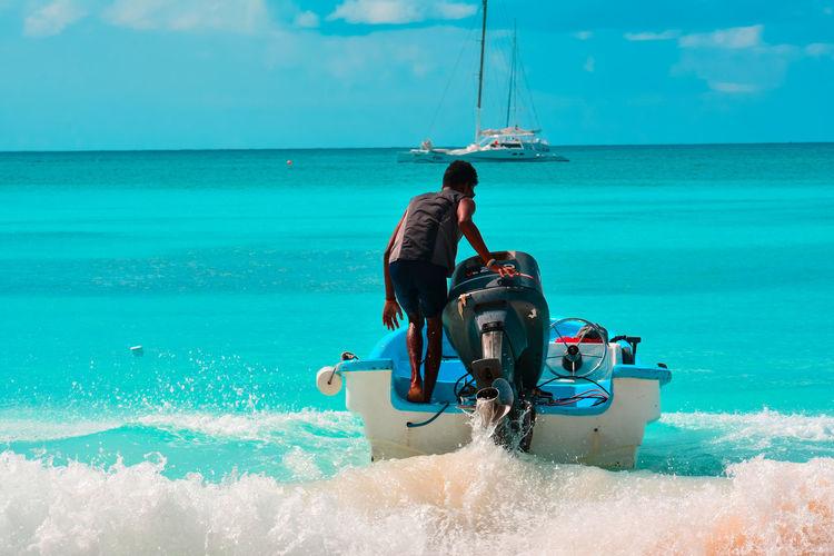Rear View Of Man In Motorboat Against Sky