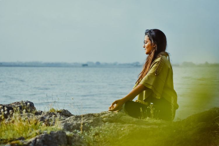 Side view of woman meditating while sitting by sea against sky
