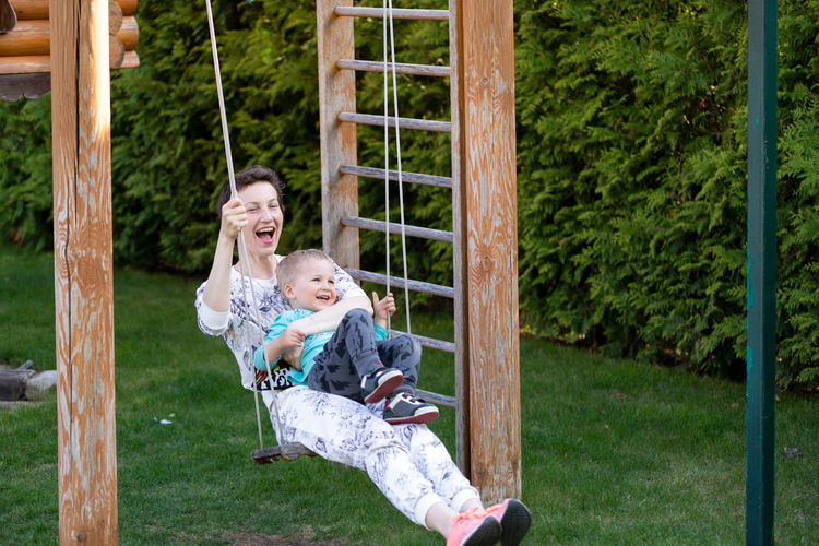 Cheerful mother and son swinging in park