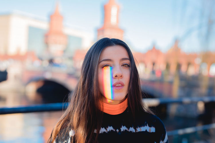 Portrait of young woman with spectrum of face in city