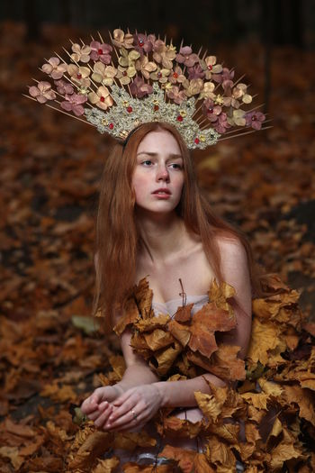 Thoughtful young woman wearing flowers on hair sitting at forest during autumn