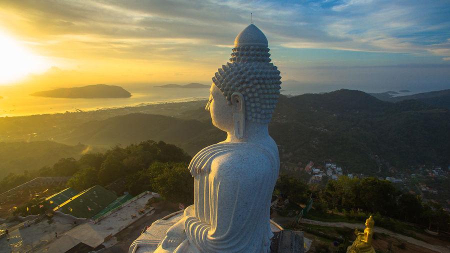 Tall Buddha Statue Against Cloudy Sky During Sunrise