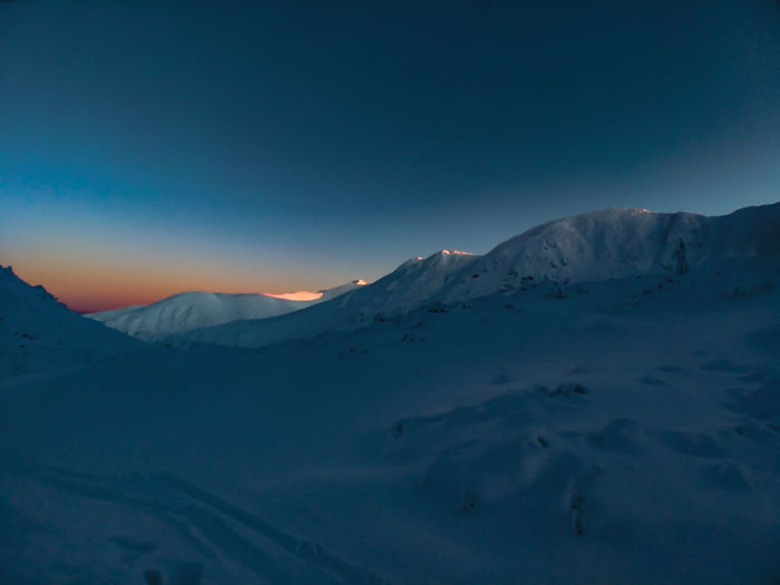 Scenic view of snowcapped mountains against sky during last faze of sunset