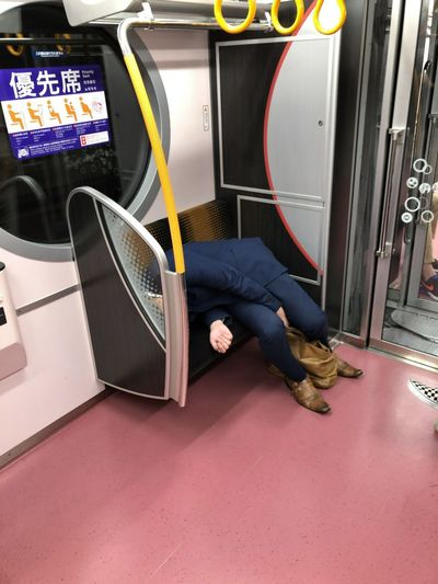 Low section of man sitting in train