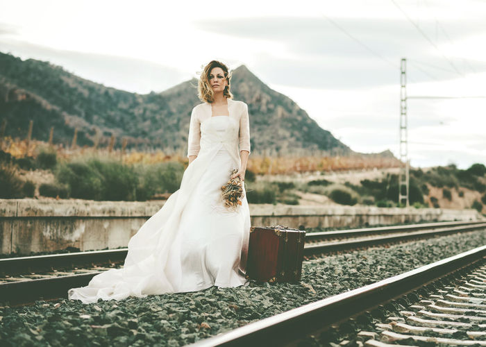 Thoughtful bride standing on railroad track