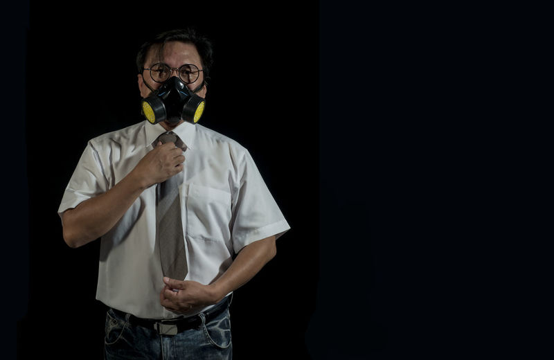 Portrait of businessmen wearing gas masks with a black background. Concept of pollution world Unhygienic Tragedy Toxic Pollution Gas Mask Disaster Ecology Environmental Conservation One Person Holding Portrait Dark Copy Space