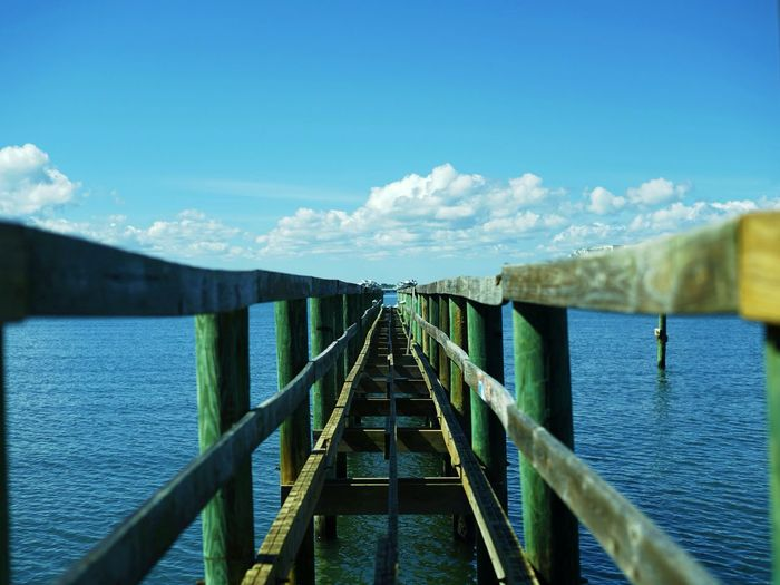 Bridge over calm blue sea against sky