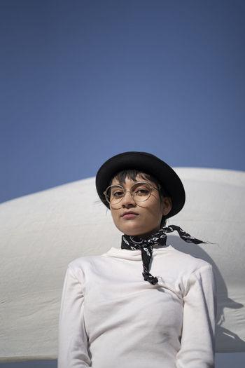 Portrait of woman wearing hat against sky in winter