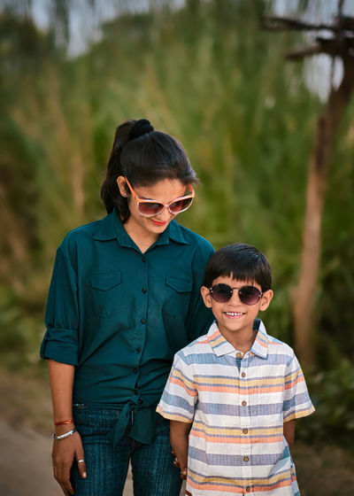 Mother and son wearing sunglasses standing outdoors