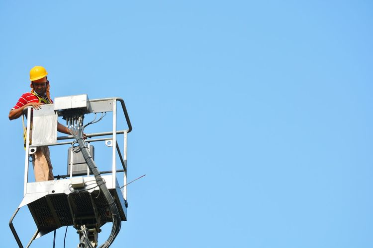 Low angle view of technician standing on hydraulic platform against clear sky