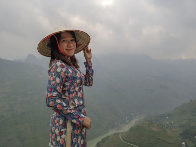Young Vietnamese women facing and pose for camera with stunning view of the Nho Que river surrounded by mountains from the Ma Pi Leng pass in northern Vietnam Mountain Cloudy Green Color Meo Vac Vietnam Vietnamese Ao Dai Beauty In Nature Casual Clothing Clothing Cloud - Sky Day Environment Females Freedom Hat Landscape Leisure Activity Mountain Mountain Range Nature One Person Outdoors People Portrait Pose Scenics - Nature Sky Standing Sunrise Three Quarter Length Traditional Dress Valley Women