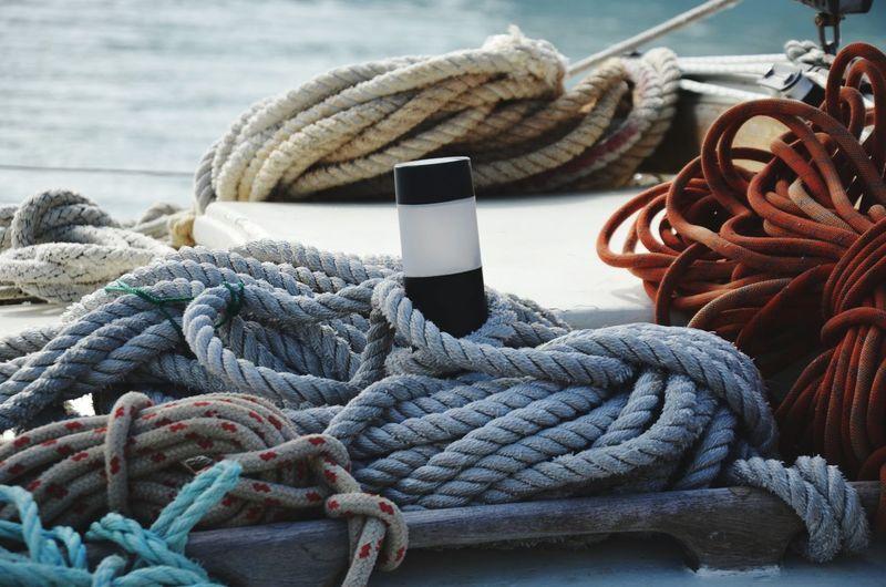 Close-up of ropes tied to bollard at harbor